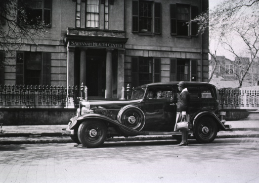 <p>Exterior view of the Savannah Health Center.  An African American nurse is standing by an automobile that is used to transport nurses to the districts under their care.</p>