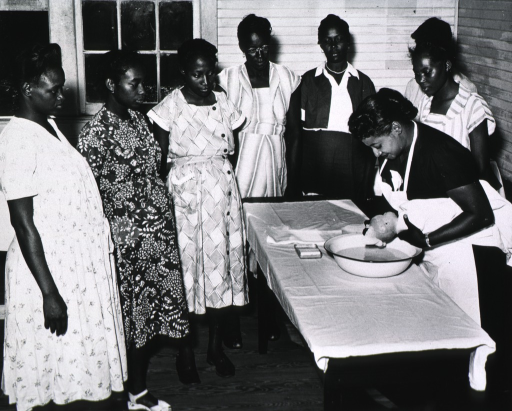 <p>Seven African American women receive instructions from Eugenia Broughton as she demonstrates how to bath an infant.</p>