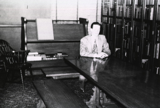<p>Interior view:  Book shelves line the wall at the Cleveland Branch incunabula room.  Behind a man sitting at the end of a table is an oversized book stand.</p>