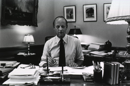 <p>Donald Fredrickson, director of the National Institutes of Health, is seated at his desk with pen in hand.  On the desk are glasses, a coffee cup, a pen set, a container of pencils, three books in a bookend, a lamp, and a great deal of paper.  Behind him there is a table with a dial telephone, a binder, piles of paper, a ball on a stand, and a lamp.  Framed pictures are on the wall over the table.  A small table with a lamp is under a painting on the wall.</p>