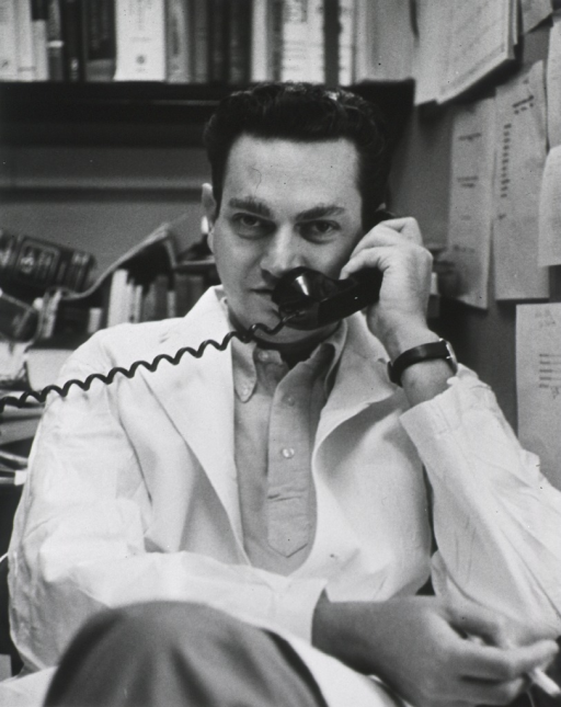 <p>Three-quarter length, full face, seated at desk, holding telephone receiver; smoking.</p>