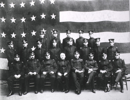 <p>Class is in front of a large flag.</p>