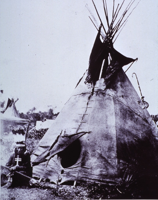 <p>A medicine-man sitting to the left of the entrance to his tepee.</p>