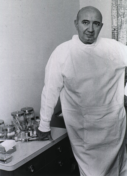 <p>Three fourths length, full face; standing in lab gown in examining office.</p>