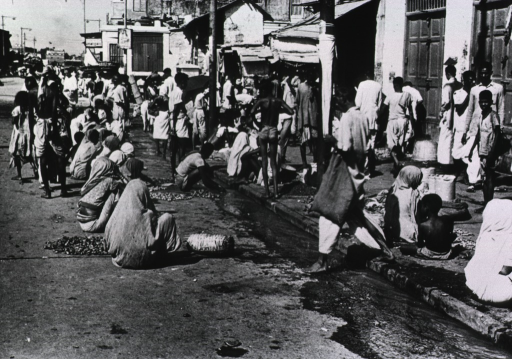 <p>A crowded city street; many people are sitting in the street and some are washing things in the water flowing in the gutter.</p>