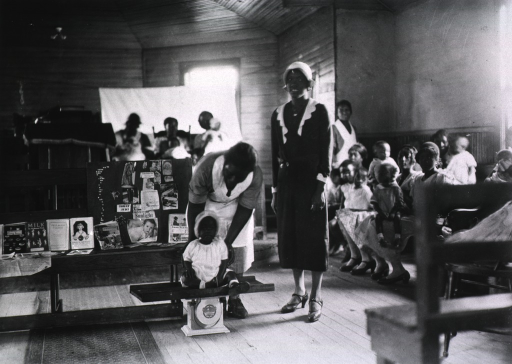 <p>Preschool child is weighed by African American nurse at an improvised baby station and child health clinic set up in a church.  African American mothers and babies are sitting in the background.  There is an exhibit on a table behind the scale.</p>