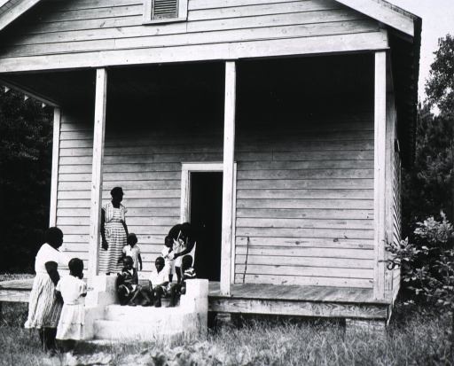 <p>Children are sitting on the steps of the school clinic.  Eugenia Broughton, an African American nurse midwife, is standing on the porch.</p>