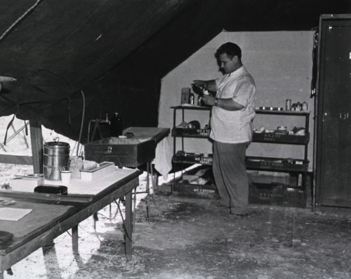 <p>A serviceman pours an indeterminate substance into another container.  Medical supplies sit on shelves behind him in the tent.</p>