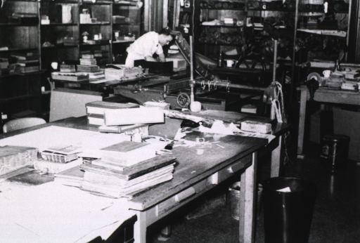 <p>Interior view: The Cleveland Branch of the History of Medicine binding studio at the National Library Binding Co.  Shelves with supplies and rare materials in need of restoration and/or repair.  In the foreground is a table with stacks of rare books.  In the background is a large paper cutter and a bindery press.</p>