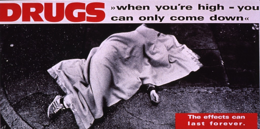<p>Predominantly b&amp;w poster with multicolor lettering and red highlights.  Title at top of poster.  Visual image is a b&amp;w photo reproduction featuring a person lying on the ground, almost completely covered by a blanket.  Only a hand and a foot are visible.  It is not clear if the person is sleeping in the street or dead.  Caption in lower right corner; publisher information in lower left corner.</p>