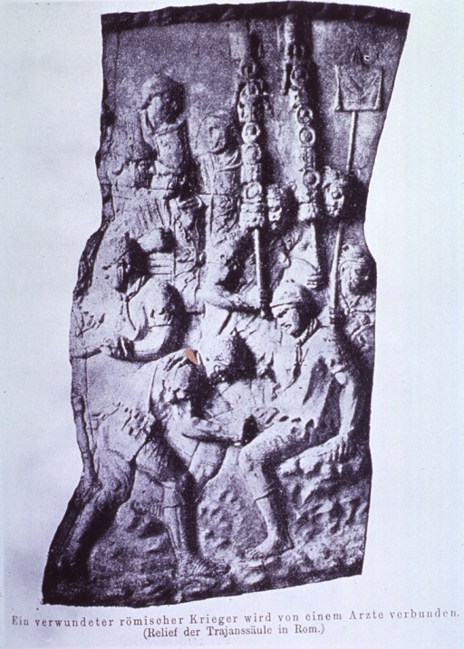 <p>Photograph of section of relief from Pillar of Trajan, Rome, showing a physician bandaging a wounded Roman Soldier.</p>