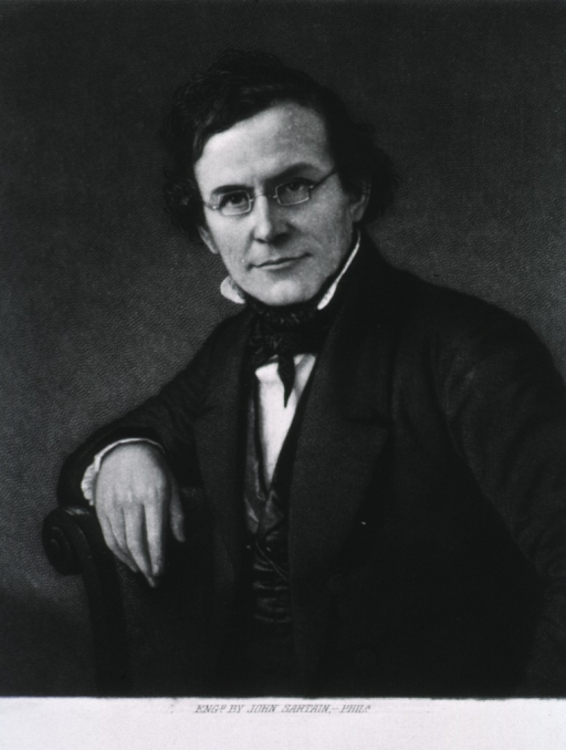 <p>Half-length, seated, left pose, full face; wearing glasses; arm over back of chair.</p>