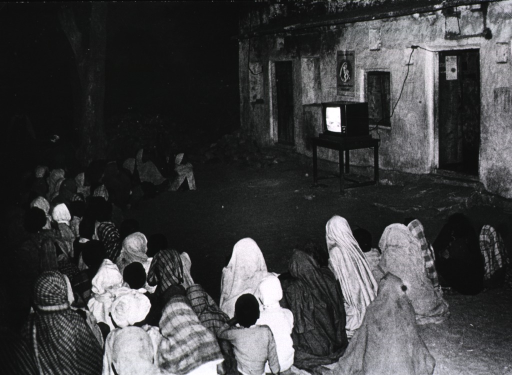 <p>A television set, placed on a table just outside a building, flickers into the night as a large group of people are gathered in front, sitting on the ground, watching it.</p>