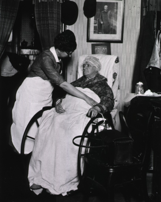 <p>Showing a nurse attending to an old woman in a wheelchair.</p>