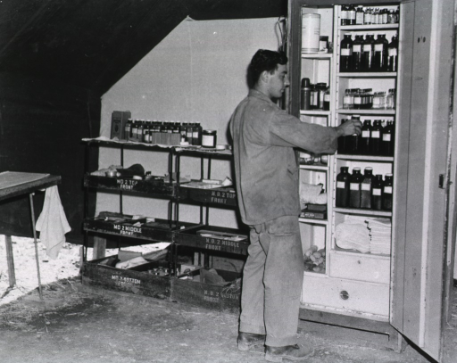 <p>A serviceman removes a bottle from a cabinet stocked with bottles and other supplies.</p>