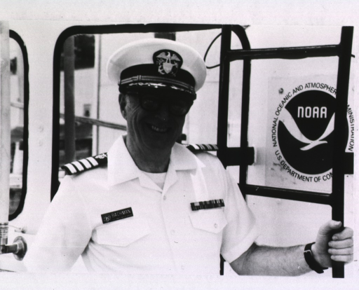 <p>Head and shoulders, right pose, wearing uniform, cap, and glasses; left hand on ladder next to NOAA emblem.</p>