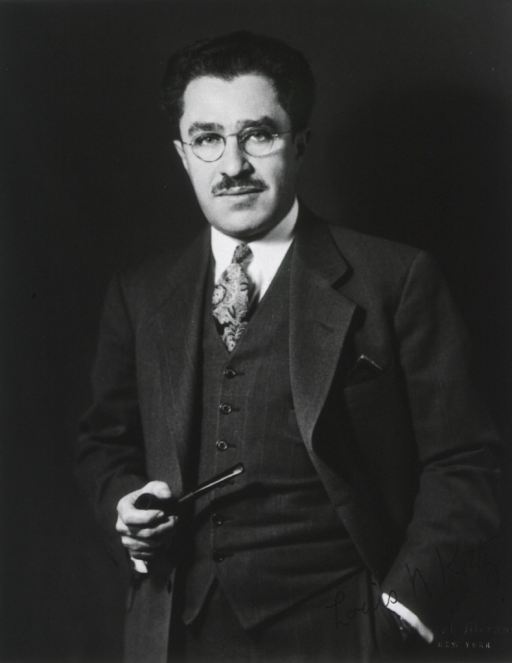 <p>Half-length, standing, left pose, full face; holding pipe in right hand, left hand in pocket; wearing glasses.</p>