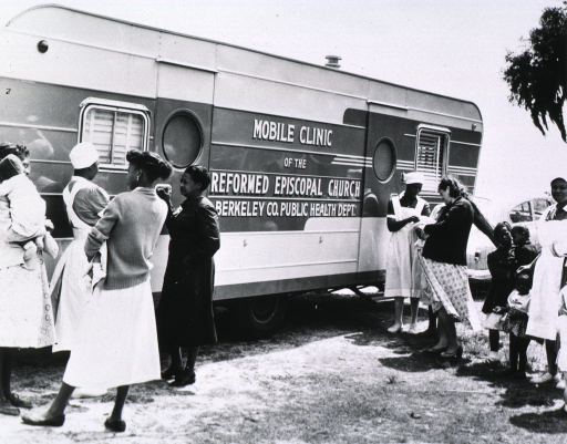 <p>Eugenia Broughton, RN, an African American nurse midwife stands among patients and nurse midwives outside of the Mobile Clinic of the Reformed Episcopal Church, Berkeley Co. Public Health Dept.</p>