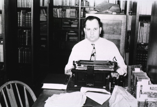<p>Interior view:  In the Cleveland Branch of the History of Medicine a man is sitting at a table with a typewriter and books.  The stacks are in background and on each side of the man.</p>