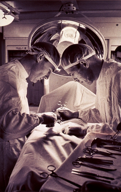 <p>Two male surgeons are performing surgery in an operating room.  A third man is in the background, his head uncovered.  A tray of surgical instruments is at hand and each surgeon has a instrument in his hand.  There is a big surgical light fixture directly over the patient.</p>