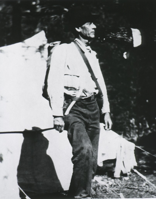 <p>Full length, standing, right pose; wearing camping clothes and backpack, tent in background.</p>