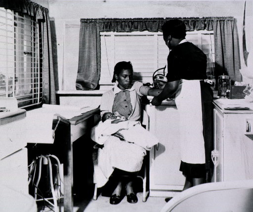 <p>Interior view of the Mobile Clinic of the Reformed Episcopal Church, Berkeley Co. Public Health Department.  Miss Broughton, an African American nurse midwife, is taking the blood pressure of a woman holding her infant.</p>