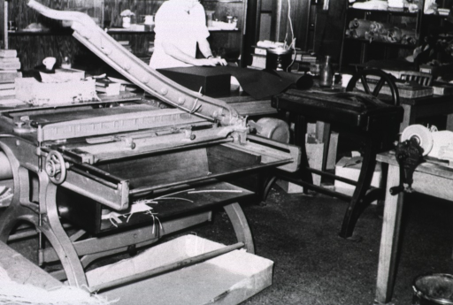 <p>Interior view: A large paper cutter and a bindery press in the Cleveland Branch HMD binding studio at the National Library Binding Co.  In the background are shelves and rare materials in need of restoration and/or repair.</p>