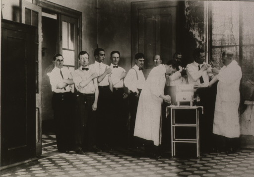 <p>Interior view: eight men are standing in a line.  One man in a lab coat is inocculating a man in line  while a second man in a lab coat is filling a syringe.</p>