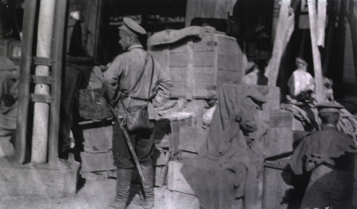 <p>Men wait outside the railroad station in Harbin.  Crates are piled high.</p>
