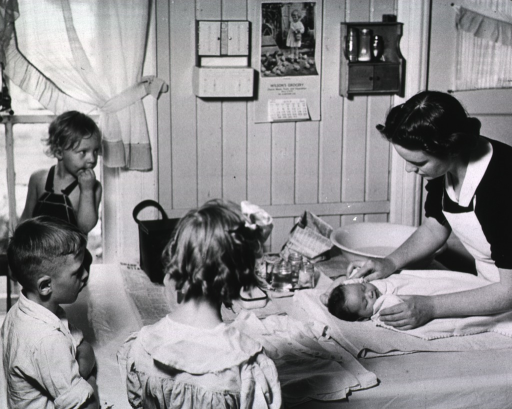 <p>Showing a nurse bathing a baby as three other children stand around the table watching.</p>