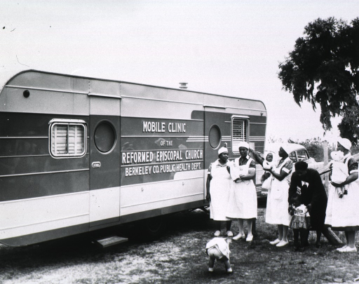 <p>Eugenia Broughton, an African American nurse-midwife at the Mobile Clinic of the Reformed Episcopal Church, Berkeley Co. Public Health Department is standing outside with patients.</p>