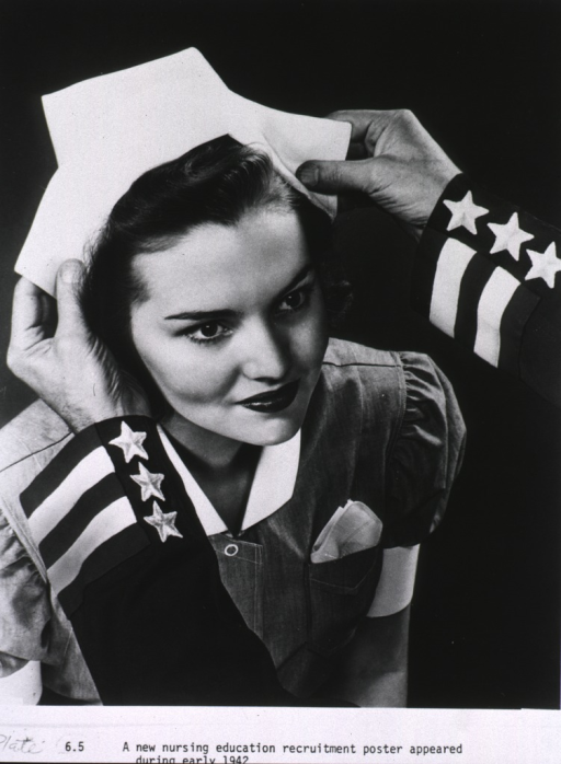 <p>Right pose, head and shoulders of a woman in nurse uniform as she receives her cap which is being placed on her head.</p>