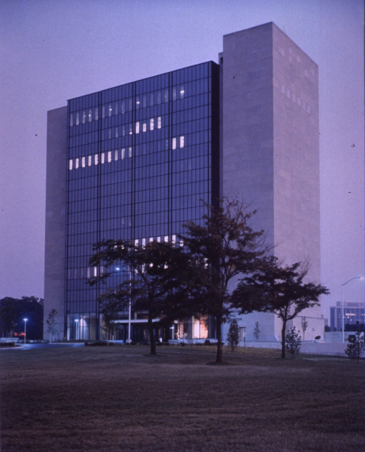 <p>Lights are on at the lobby level and on several floors of the Lister Hill Center.  Grass and three trees are in the foreground with several smaller trees around the building.  Street lights are on each side of the building.</p>