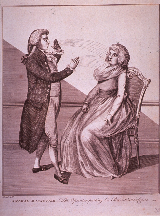 <p>A man, a hypnotist, is attempting to hypnotize a woman sitting in a chair. Her arms hang limp as she stares into a space defined by the movement of his hands.</p>