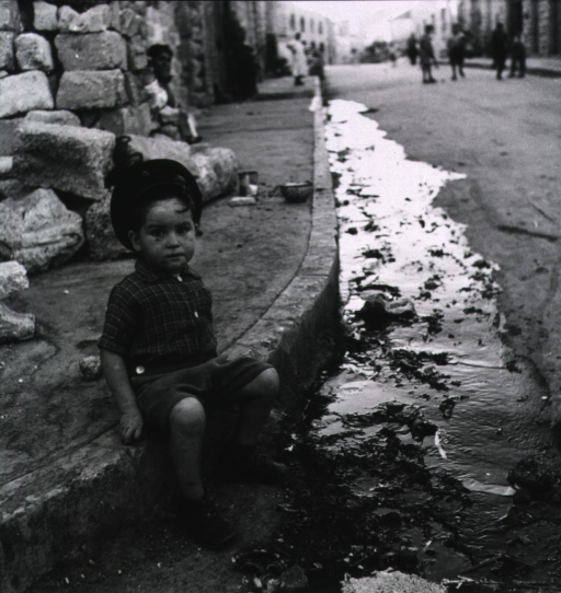 <p>A young boy is sitting on the curb along a street; trash flows with the water in the gutter.</p>