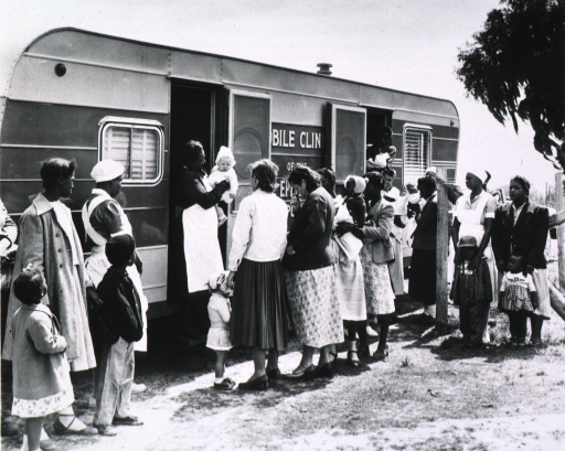 <p>Eugenia Broughton, an African American nurse midwife, is holding a child as she stands in the doorway of the Mobile Clinic of the Reformed Episcopal Church, Berkeley Co. Public Health Dept.</p>