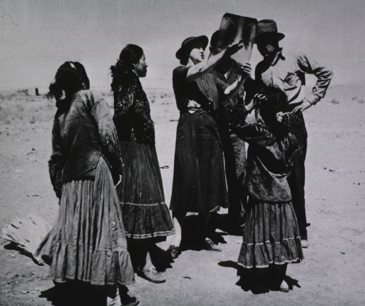 <p>A group of four Navajo adults and one child stand near a nurse who is holding a chest x-ray and, pointing to the lungs, tells the two men in the group how x-rays are used in the tuberculosis control program.</p>