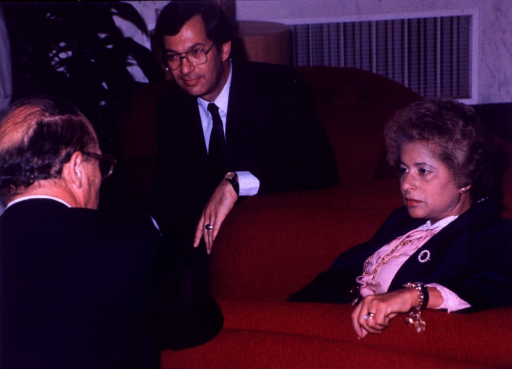 <p>Vincent DeVita, Jr., incoming director of the National Cancer Institute (NCI), and Patricia Roberts Harris, secretary of the Dept. of Health and Human Services (DHHS) are sitting in large red chairs looking at Donald Fredrickson, director of the National Institutes of Health (NIH).</p>