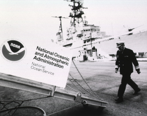 <p>Full length, left view of Surgeon General Koop as he approaches the gangplank; NOAA emblem mounted on the ramp. Another ship is visible in the background.</p>