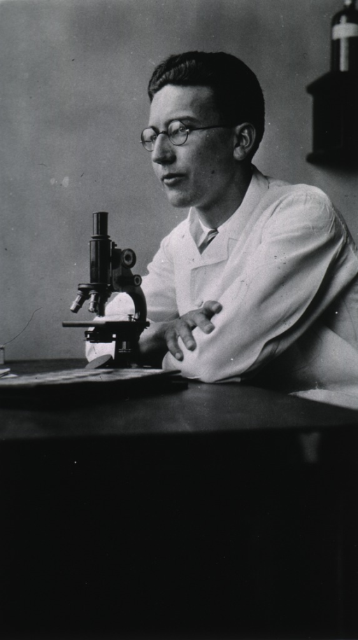 <p>Seated, at microscope, in laboratory.</p>