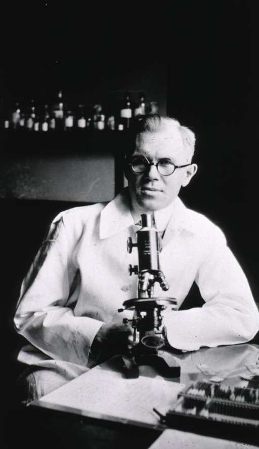 <p>Half length, full face, seated at microscope, wearing white coat.</p>
