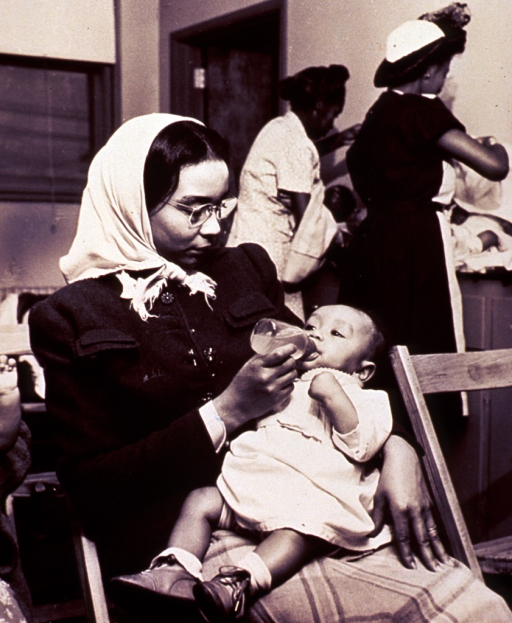 <p>African American woman (three-quarter length portrait, seated, facing right) bottle-feeding her infant in a waiting room; two African-American women in the background appear to be changing diapers on two infants.</p>