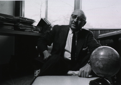 <p>Three-quarter length, seated at desk, full face; small globe on desk.</p>