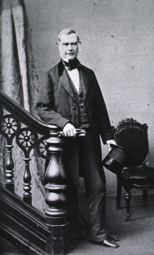 <p>Full length, standing, full face; arm resting on banister; holding gloves and top hat.</p>