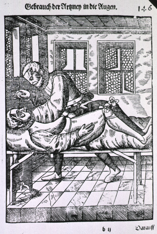 <p>A man lying on a table is being examined and/or treated by an ophthalmologist.</p>