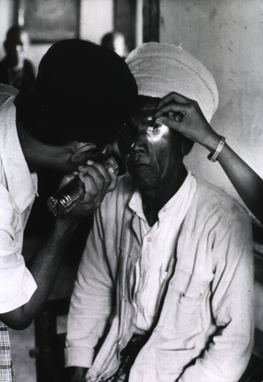 <p>An old man is sitting for an eye examination; a man using a flashlight examines the left eye while an assistant holds the eye open.</p>