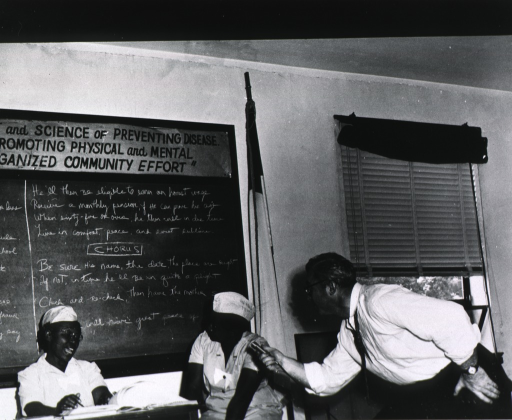 <p>View of Broughton and two other African American women in a classroom in front of the blackboard.</p>