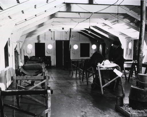 <p>A serviceman wearing a stethoscope tends to a patient on a hospital bed.  Other makeshift beds stand against the walls of the ward.</p>