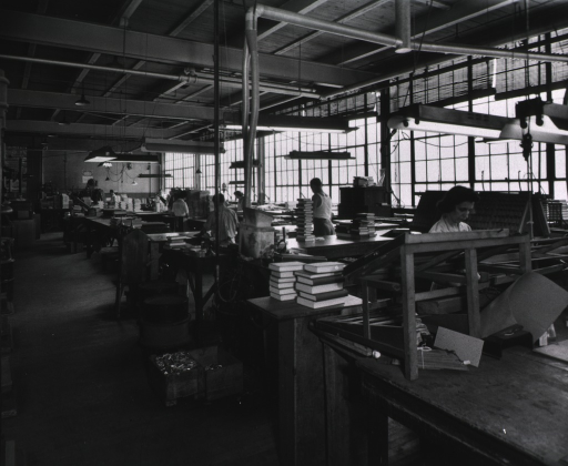 <p>Interior view: Some National Library Bindery Company employees working at tables stacked with bound books.</p>