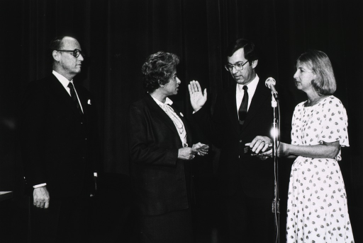 <p>Patricia Roberts Harris, secretary of the Dept. of Health and Human Services (DHHS), is holding a card in her hands.  Vincent DeVita, Jr. is raising his right hand with his left hand on a book held by Mrs. DeVita.  A microphone is between Dr. and Mrs. DeVita.  Dr. Fredrickson, director of the National Institutes of Health, is standing beside Secretary Harris.</p>